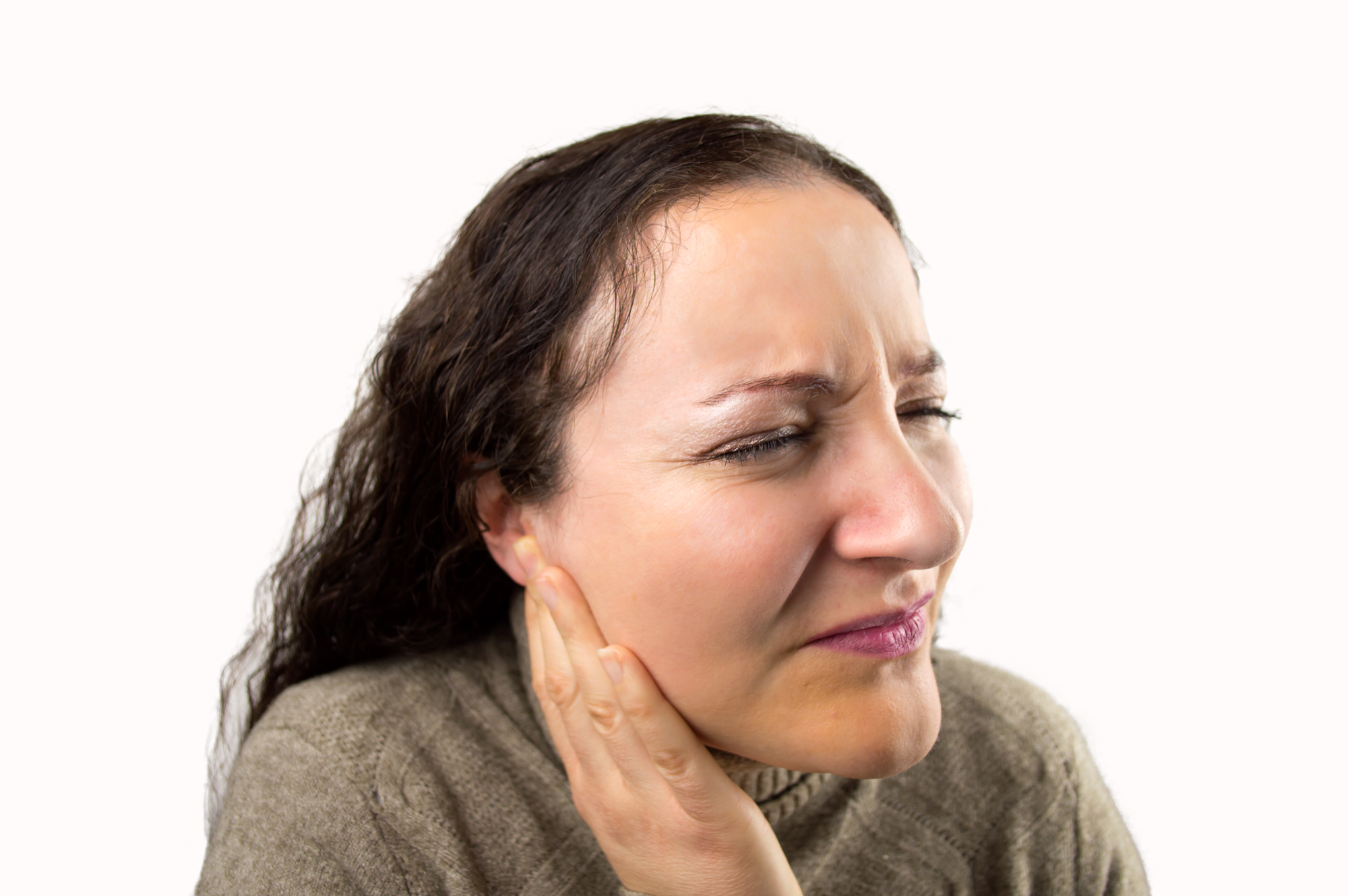 closeup of a woman with a severe ear pain with white background